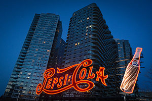 Pepsi Cola neon sign with bottle in front of skyscrapers